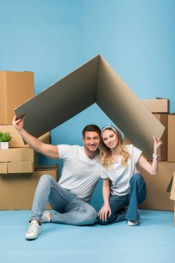 cheerful couple holding carton roof over heads while sitting on blue with cardboard boxes for relocation