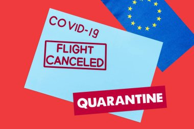 Top view of blue envelope with covid-19, flight canceled and quarantine lettering near european union flag isolated on red stock vector