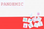 top view of pandemic lettering near medical drawn pictures on polish flag