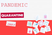 top view of pandemic, quarantine and covid-19 lettering near drawn medical pictures on polish flag