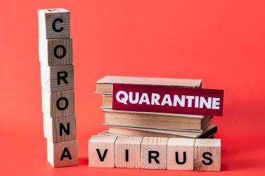 Wooden cubes with coronavirus near books and quarantine lettering on red stock vector