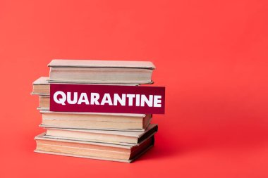 books and card with quarantine lettering on red with copy space