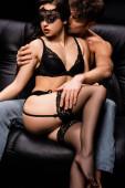 sexy Frau in schwarzen Dessous mit schwarzem Spitzenband auf den Augen sitzt auf dem Sofa mit leidenschaftlichem Mann isoliert auf schwarz
