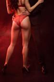 oříznutý pohled na muže objímání sexy žena v červené spodní prádlo na černé s červeným světlem