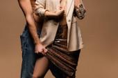 oříznutý pohled na muže bez trička a sexy polonahou ženu v sukni a bundě izolované na béžové