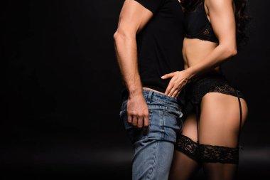 cropped view of seductive girlfriend in black lingerie undressing boyfriend on black