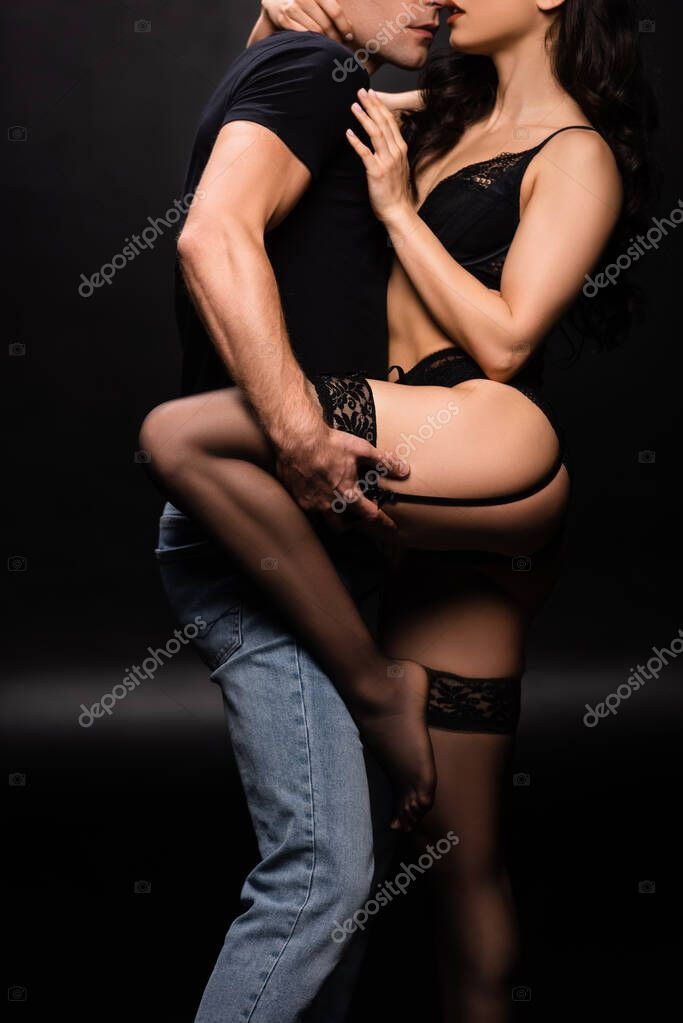 Cropped view of beautiful sexy couple hugging on black stock vector