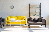 Wohnzimmer mit gelbem Sofa, grauen Sesseln, Regal, Uhr und Laptop im Sonnenlicht