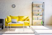 obývací pokoj se žlutou pohovkou, police a stůl s notebookem na slunci