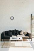Wohnzimmer mit grauem Sofa, Regal und Tisch mit Laptop im Sonnenlicht