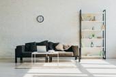 Fotografie Wohnzimmer mit grauem Sofa, Uhr, Regal und Tisch mit Laptop im Sonnenlicht