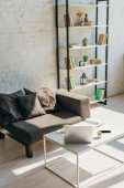 Photo living room with grey sofa, shelf and table with laptop, smartphone and notepad in sunlight