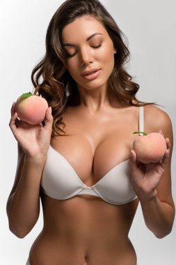 sexy, pensive girl with big breasts and closed eyes holding ripe peaches isolated on white
