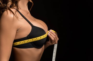 cropped view of sexy girl measuring breasts with measuring tape isolated on black