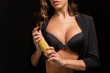 Cropped view of seductive girl with big breasts holding corn ear isolated on black stock vector