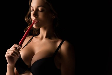 sexy girl with big breasts touching lips with red hot chili pepper isolated on black