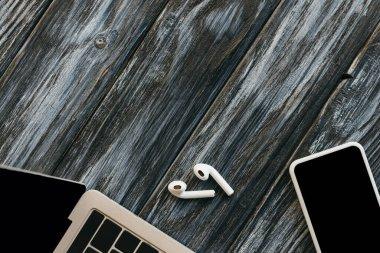 Top view of laptop, smartphone and earphones on dark wooden surface stock vector