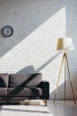 obývací pokoj s pohovkou, hodinami a lampou na slunci