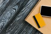 top view notepad, hitelkártya és okostelefon üres képernyővel sötét fa felületen