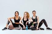 Multikulti-Mädchen sitzen mit Sportgeräten auf weiß