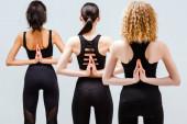 Rückansicht multikultureller Frauen in umgekehrter Gebetspose isoliert auf Weiß