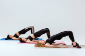 multikulturní dívky dělají bridž cvičení na fitness rohože izolované na bílém