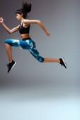 Seitenansicht eines afrikanisch-amerikanischen Mädchens in Sportbekleidung, das auf grau springt