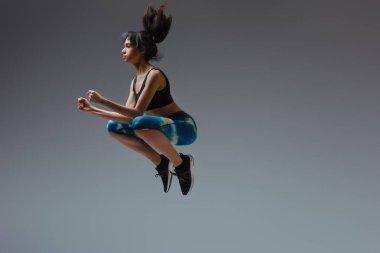 Spor kıyafetli Afro-Amerikan kız griye atlıyor.