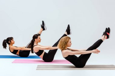 multicultural women exercising on fitness mats isolated on white