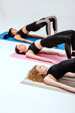 selective focus of multicultural girls doing bridge exercise on fitness mats on white