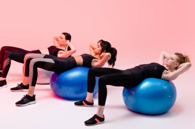 multicultural girls exercising on fitness balls on pink