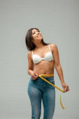 Fotografie šťastný a nadváha africký americký dívka v džínách a podprsenka měření pas izolované na šedé