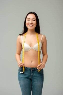 cheerful and overweight asian girl holding measuring tape isolated on grey
