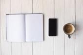 Horní pohled na šálek kávy, smartphone a notebook na dřevěném pozadí