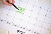 Ausgeschnittene Ansicht einer Frau, die mit Stift auf Fitness-Schriftzug im To-Do-Kalender mit der Aufschrift 2020 auf Holzgrund zeigt