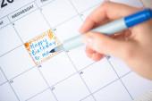 Oříznutý pohled ženy ukazující značkovacím perem na šťastné narozeniny na mě, jak píšu do kalendáře