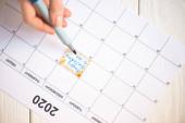 Oříznutý pohled ženy ukazující značkovacím perem na všechno nejlepší k narozeninám, nápis do kalendáře s nápisem 2020 na dřevěném pozadí
