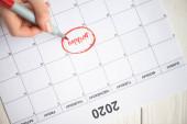 Ausgeschnittene Ansicht einer Frau, die mit Filzstift auf Geburtstagsbuchstaben im To-Do-Kalender mit der Aufschrift 2020 auf Holzgrund zeigt