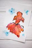 Fotografie Papieroberseite mit japanischer Malerei mit orangefarbenen Fischen auf Holzgrund
