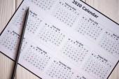 Horní pohled na kalendář 2020 a tužku na dřevěném pozadí