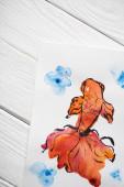 Horní pohled na papír s japonskou malbou s oranžovou rybou na dřevěném pozadí