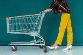 oříznutý pohled na módní ženu ve žluté masce kráčející s prázdným nákupním vozíkem na modré