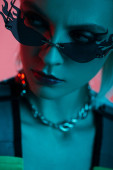 stylish female model in futuristic leotard and fire-shaped sunglasses posing isolated on pink in blue light