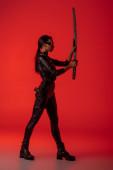 boční pohled na futuristické africké americké ženy v brýlích s mečem na červeném pozadí