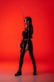 atraktivní futuristický africký Američan žena v brýlích s mečem na červeném pozadí