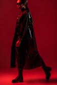 futuristický africký americký žena v brýlích chůze na červeném pozadí