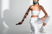 futuristická africká americká žena v bezpečnostní masce s pistolí na bílém pozadí