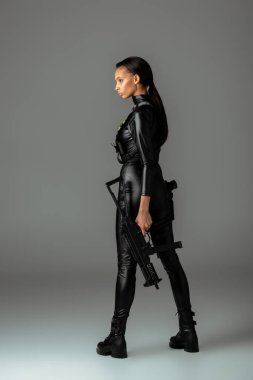 Futuristic african american woman posing with assault rifle isolated on grey stock vector