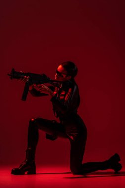 Futuristic african american woman in glasses aiming assault rifle on red background stock vector