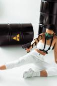 Fényképek futurisztikus afro-amerikai nő biztonsági maszkban célzás pisztoly közelében radioaktív hulladék hordók fehér háttér